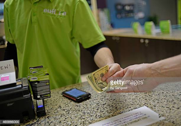 A customer pays for his marijuana at Euflora Dispensary in Denver March 11 2015 Colorado pot sales soar to record in January bringing $23 million for...
