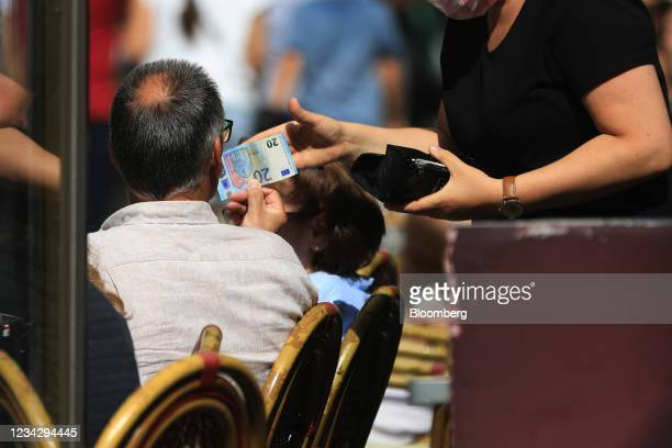 Customer pays for lunch on a restaurant terrace in Berlin, Germany, on Thursday, July 29, 2021. Germany reports gross domestic product figures on...