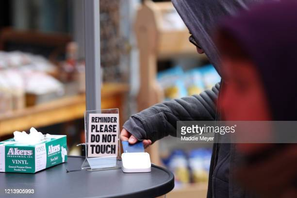 Customer pays for their groceries at the Safe Supply outdoor grocery store at Bow Market on March 21, 2020 in Somerville, Massachusetts. In order to...