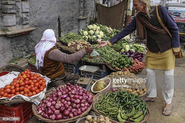 A customer pays for vegetables at a stall in Varanasi Uttar Pradesh India on Friday Dec 9 2016 India is scheduled to release Consumer Price Index...