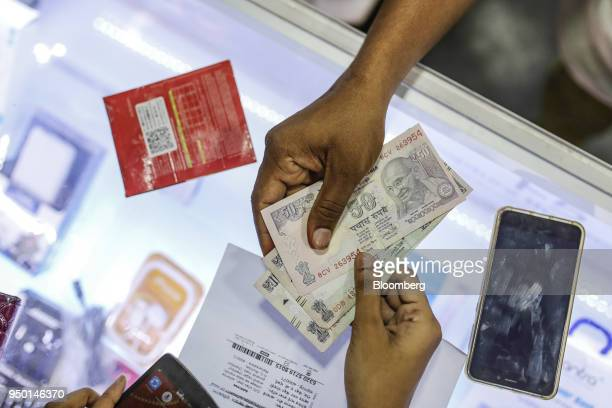 A customer pays Indian Rupee banknotes to a vendor at a sim card store in Mumbai India on Saturday April 21 2018 Bharti Airtel are scheduled to...