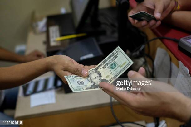 A customer pays with a twenty US dollar bill at a bakery shop on June 26 2019 in Caracas Venezuela Everyday more Venezuelans use American dollar...