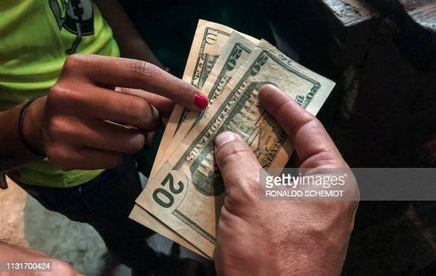 A customer pays with US dollars at a restaurant in Caracas on March 18 2019 Whether paying for a manicure an evening gown or a liter of milk in...