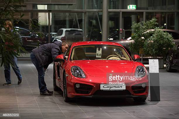 A customer peers at the interior of a Porsche Cayman sportscar for sale inside a Porsche AG luxury automobile dealership in Moscow Russia on Monday...