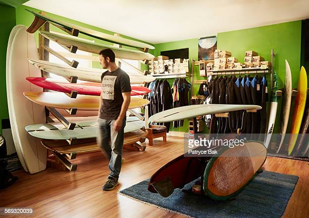 customer peruses boards at a maine surf shop. - sports equipment stock pictures, royalty-free photos & images