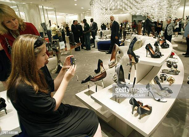 A customer photographs a display of heels as Saks Fifth Avenue unveils 17 August 2007 '10022SHOE' the new designer shoe floor that's so big it has...