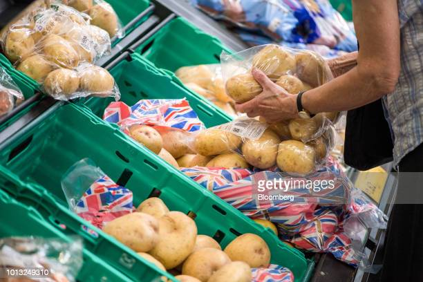 A customer picks a bag of potatoes inside a Morrisons supermarket operated by Wm Morrison Supermarkets Plc in London UK on Wednesday Aug 8 2018...