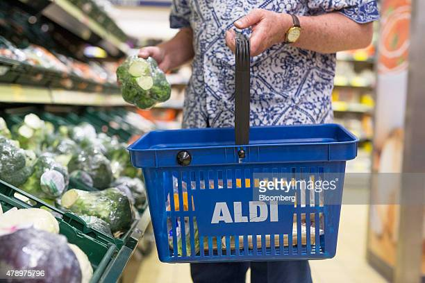 A customer picks a bunch of Broccoli from the vegetable display as he carries a blue plastic shopping basket inside an Aldi supermarket store in...