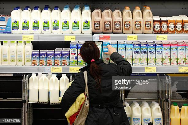 A customer picks up a carton of Farmdale Light Milk at an Aldi Stores Ltd food store in Sydney Australia on Thursday June 25 2015 Australia's biggest...