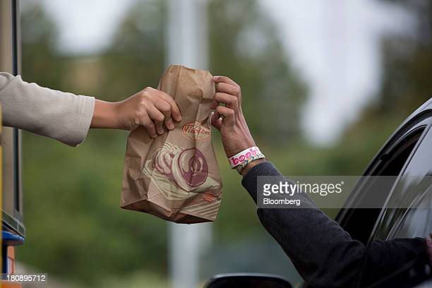 A customer picks up an order at the drivethru of a Tim Hortons Inc restaurant in Oakville Ontario Canada on Monday Sept 16 2013 Tim Hortons Inc Chief...