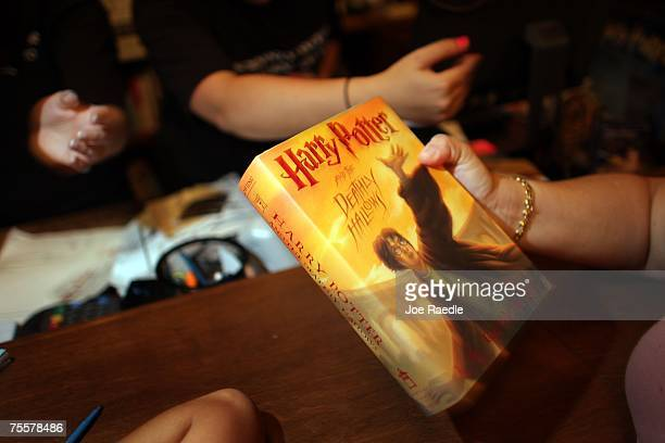 A customer picks up their new copy of Harry Potter and the Deathly Hallows after it went on sale at Books and Books July 20 2007 in Miami Florida The...