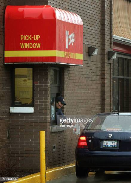 A customer picks up their order at the driveup window of a Wendy's restaurant February 15 2005 in Glenview Illinois Wendy's has introduced a new...