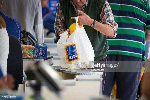 A customer places a melon into a plastic carrier bag branded with the Aldi name as they pay for goods at the checkout counter inside an Aldi...