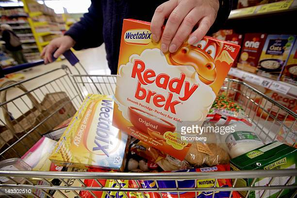 A customer places a packet of Ready brek breakfast cereal produced by Weetabix Ltd into a shopping cart in this arranged photograph at a supermarket...