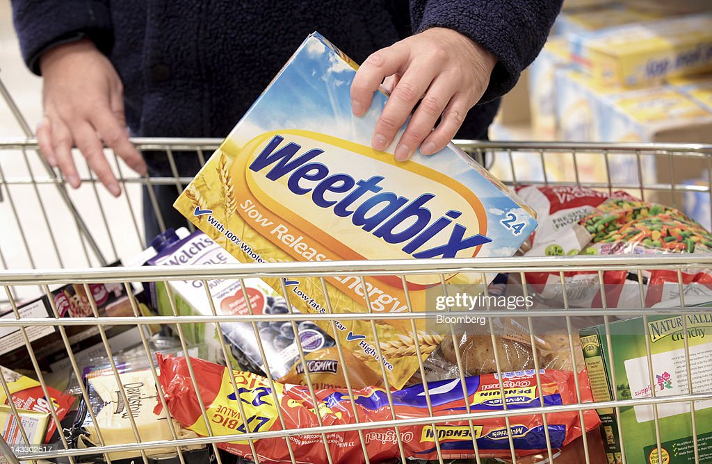 A customer places a packet of Weetabix breakfast cereal, produced by Weetabix Ltd., into a shopping cart in this arranged photograph at a supermarket in Slough, U.K., on Monday, April 23, 2012. Bright Food Group Co., China's second-largest food company, denied media reports that it is in talks to buy British cereals maker Weetabix Ltd. from private equity firm Lion Capital. Photographer: Jason Alden/Bloomberg via Getty Images