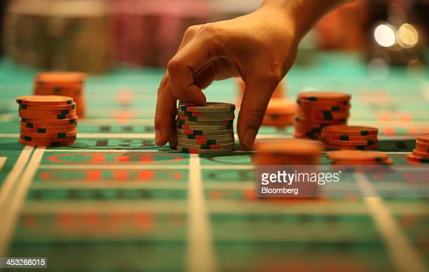 A customer places gaming chips on a roulette table at Casino Venus a mock casino operated by Japan Casino School and Bright Inc to provide the...