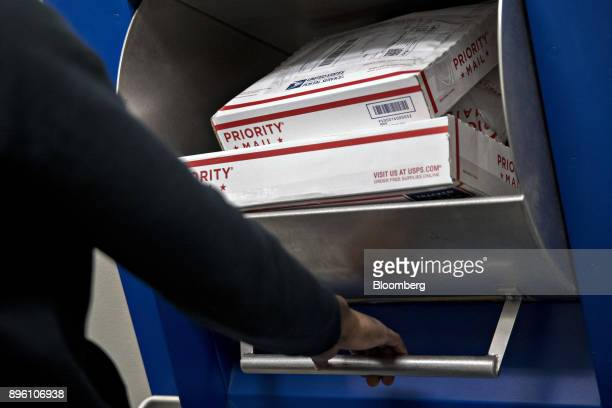 A customer places United States Postal Service priority mail packages into a dropoff bin at the USPS Suburban post office station in Gaithersburg...