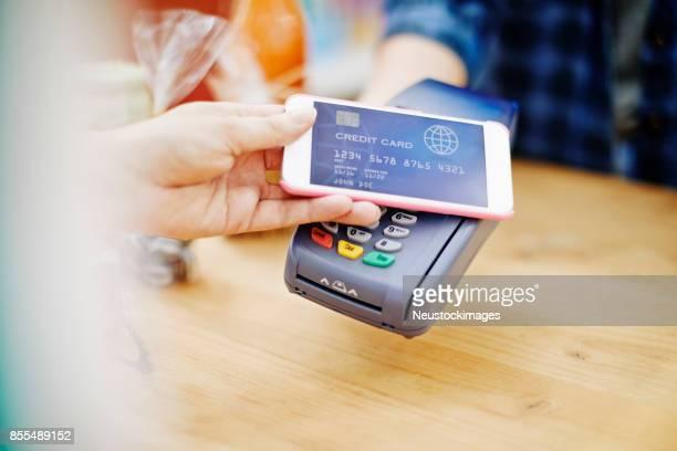 Customer placing smart phone over credit card reader in delicatessen