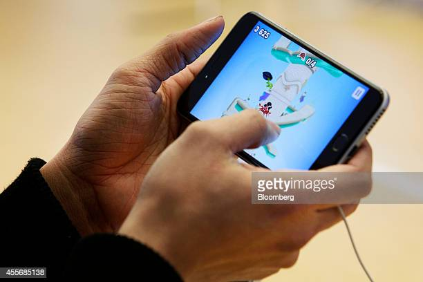 Customer plays a game on an iPhone 6 at the Apple Inc. George Street store during the sales launch of the iPhone 6 and iPhone 6 Plus in Sydney,...