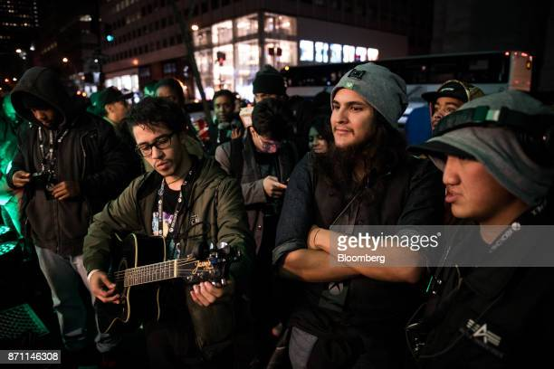 A customer plays a guitar while lining up for the Microsoft Corp Xbox One X game console global launch event in New York US on Monday Nov 6 2017 As...