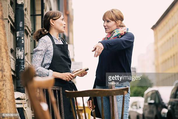 Customer pointing while having communication with owner outside antique shop