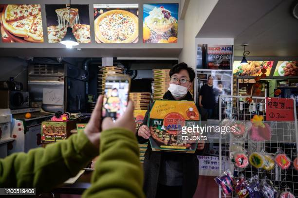 A customer poses before a photo of film director Bong Joonho at the 'Sky Pizza' restaurant in Seoul on February 13 2020 Locations featured in the...