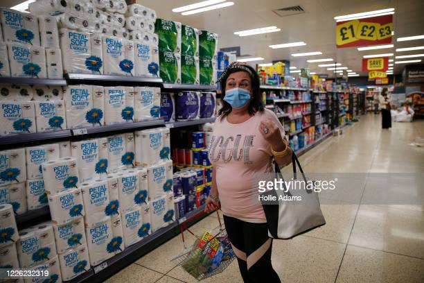 Customer poses for a photo wearing a face mask while shopping at Iceland in Islington on July 11, 2020 in London, England. On Friday, Scotland made...