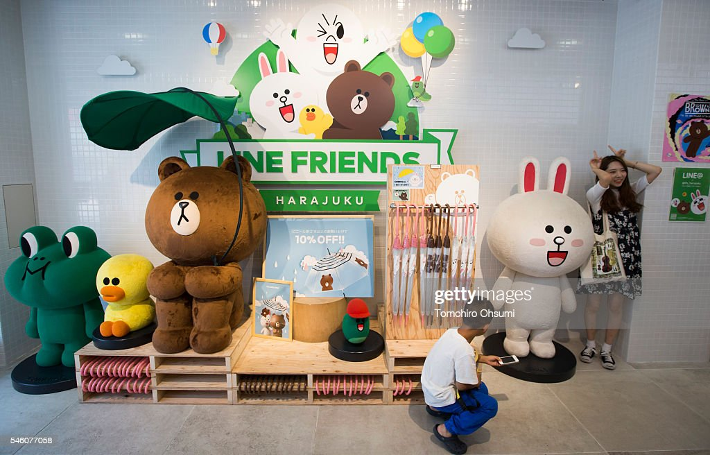 A customer poses next to characters from the Line messaging app as a boy uses a smartphone inside Line Corp.'s LINE Friends Harajuku store on July 11, 2016 in Tokyo, Japan. Japanese messaging app provider LINE Corp., owned by South Korean portal Naver Corp., announced it has set the price of its initial public offering at 35 million shares at 3,300 yen apiece on Monday. The company expects to list on the New York Stock Exchange on July 14 and also on the Tokyo Stock Exchange on July 15.