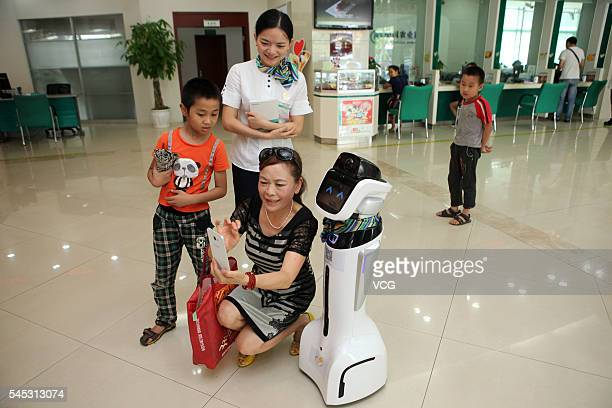 A customer poses with an intelligent robot at hall of Sichuan Neijiang Branch Agriculture Bank of China on July 7 2016 in Neijiang Sichuan Province...
