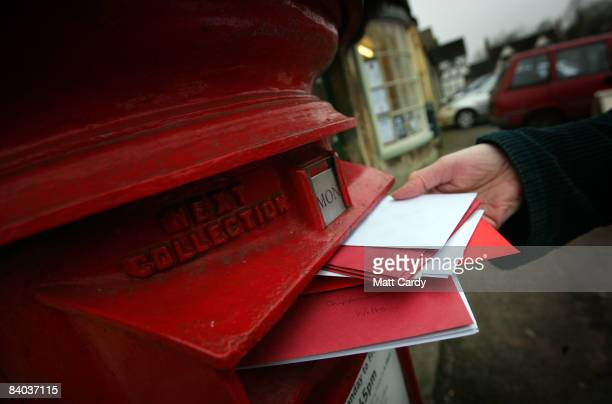 A customer posts letters in the overflowing post box outside the historic Lacock Village Stores and Post Office on December 15 2008 in Lacock United...