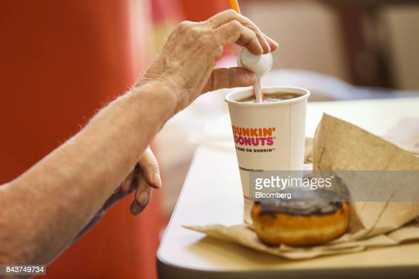 Customer pours creamer into a cup of coffee at a Dunkin' Donuts Inc. Location in Los Angeles, California, U.S., on Wednesday, Sept. 6, 2017. Dunkin'...