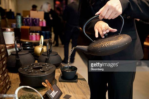 Customer pours hot water into a cup at a Teavana tea bar in New York, U.S., on Thursday, Oct. 24, 2013. Starbucks Corp., the world's largest...