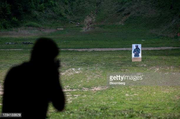 Customer practices shooting an AR-15 style rifle at a paper target depicting the image of Osama Bin Laden, deceased founder of militant organization...