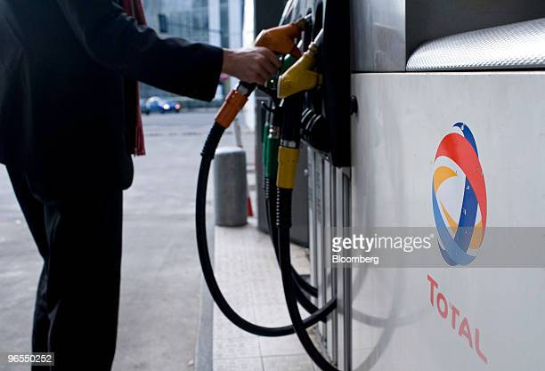 A customer prepares to fill his car with fuel at a Total SA gas station in Paris France on Wednesday Feb 10 2010 The company releases its earnings...