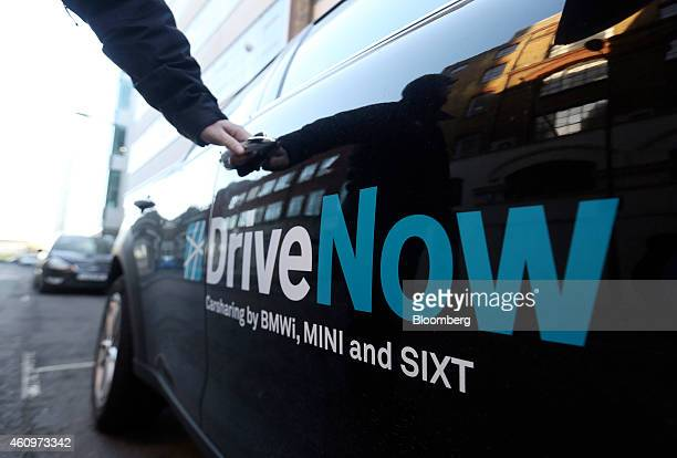 A customer prepares to open the door of a Mini Countryman automobile part of the DriveNow carsharing venture between Bayerische Motoren Werke AG and...