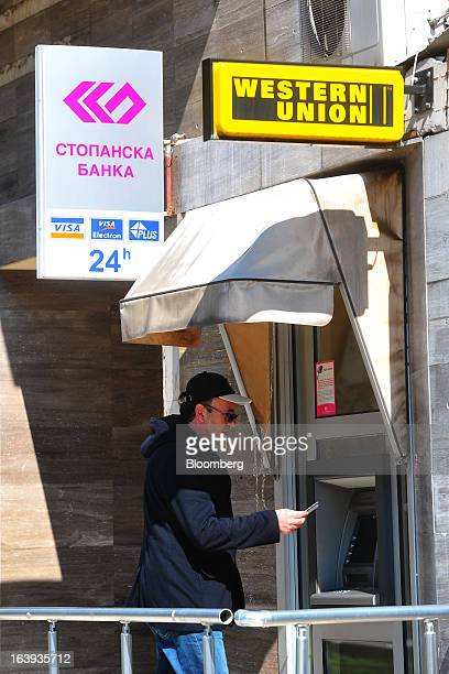 A customer prepares to use an automated teller machine operated by Stopanska Banka near a Western Union sign in central Skopje Macedonia on Sunday...
