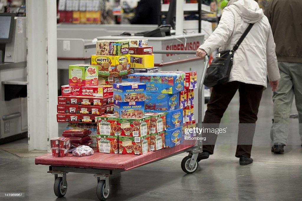 A customer pulls a cart of groceries through a BJ's