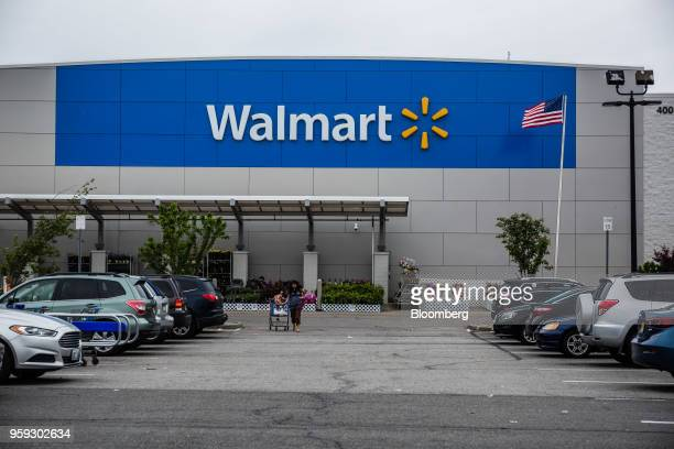 A customer pulls a shopping cart in the parking lot of a Walmart Inc store in Secaucus New Jersey US on Wednesday May 16 2018 Walmart is scheduled to...