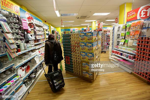 A customer pulls a wheelie shopping cart through a Poundland Group Plc store in Leigh UK on Thursday Feb 4 2016 UK like for like sales at midmarket...
