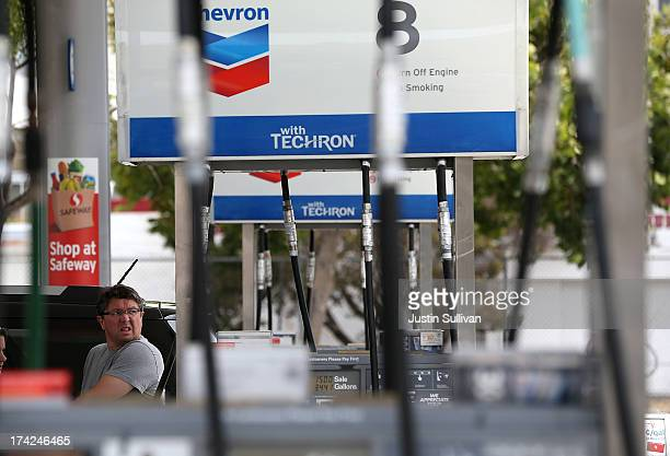 A customer pumps gas into his car at a Chevron gas station on July 22 2013 in San Francisco California According to AAA the national average price...