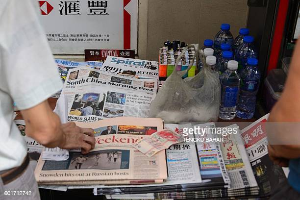 A customer purchases a pack of cigarettes as a copy of the day's South China Morning Post is seen among other newspapers at a newstand in Hong Kong...