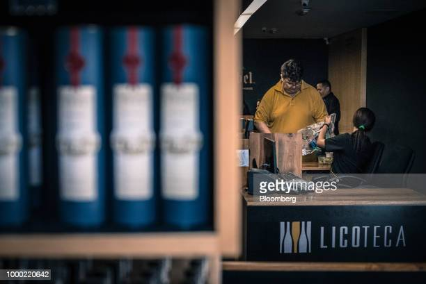A customer browses various whiskey brands on display for sale at a liquor store in the La Castellana neighborhood of Caracas Venezuela on Thursday...