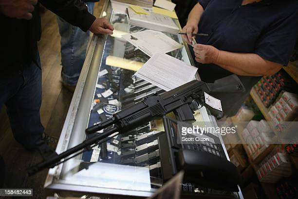 A customer purchases an AK47 style rifle for about $1200 at Freddie Bear Sports sporting goods store on December 17 2012 in Tinley Park Illinois...