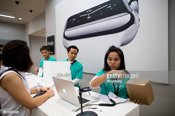A customer purchases an Apple Inc Apple Watch at an iStudio store in Bangkok Thailand on Friday July 17 2015 Apple's silence on demand for its...