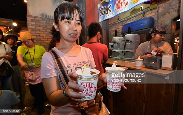 A customer purchases 'instant noodleflavoured' ice cream in a restaurant at the Cup Noodle Museum in Yokohama suburban Tokyo on August 13 2015...
