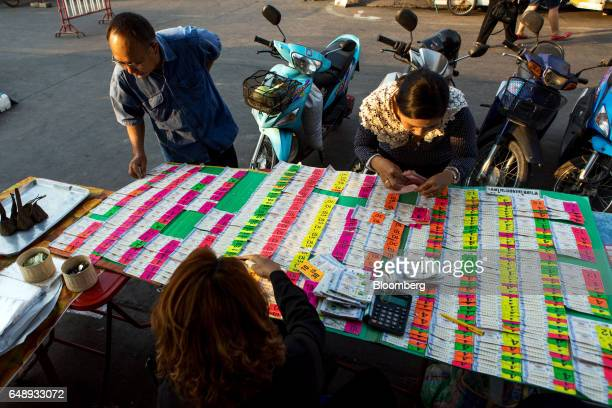 A customer purchases lottery tickets at a street market stall in Nan Nan Province Thailand on Friday March 3 2017 After more than a year of...