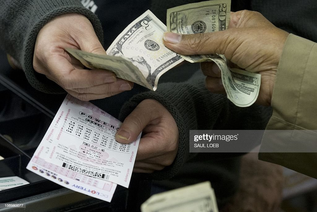 A customer purchases Powerball lottery tickets for the estimated record 425 million USD jackpot prize, Powerball's biggest winnings ever, at a convenience store in Washington on November 26, 2012. The previous drawing resulted in no winner, setting up for the record setting prize when numbers will be drawn on Wednesday. Tickets are sold in 42 US states, Washington, DC, and the US Virgin Islands. AFP PHOTO / Saul LOEB