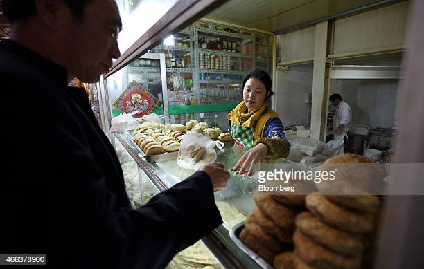 A customer purchases steamed buns from a vendor at a market stall in Beijing China on Wednesday March 4 2015 China's leaders are gathered this week...