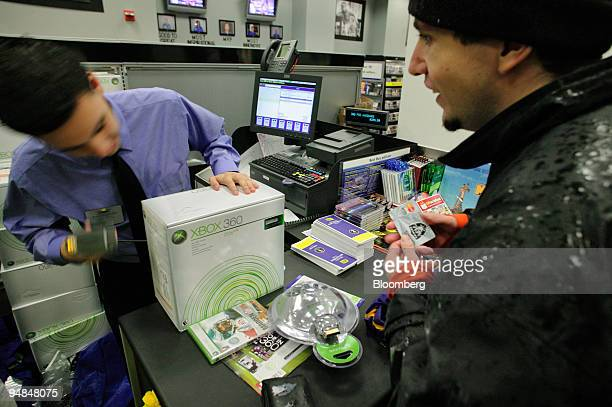 Customer purchases the new Microsoft Xbox 360 video-game console at a Best Buy store in New York, NY at 12:30am on Tuesday, November 22, 2005....