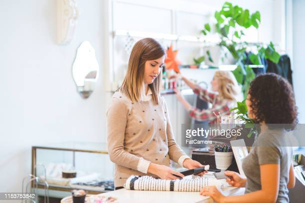 customer purchasing items at an upscale fashion boutique - opening event stock pictures, royalty-free photos & images